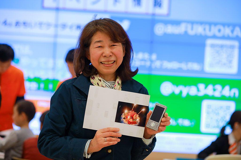 再起動したケータイとプリントアウトされた写真を手に微笑む女性