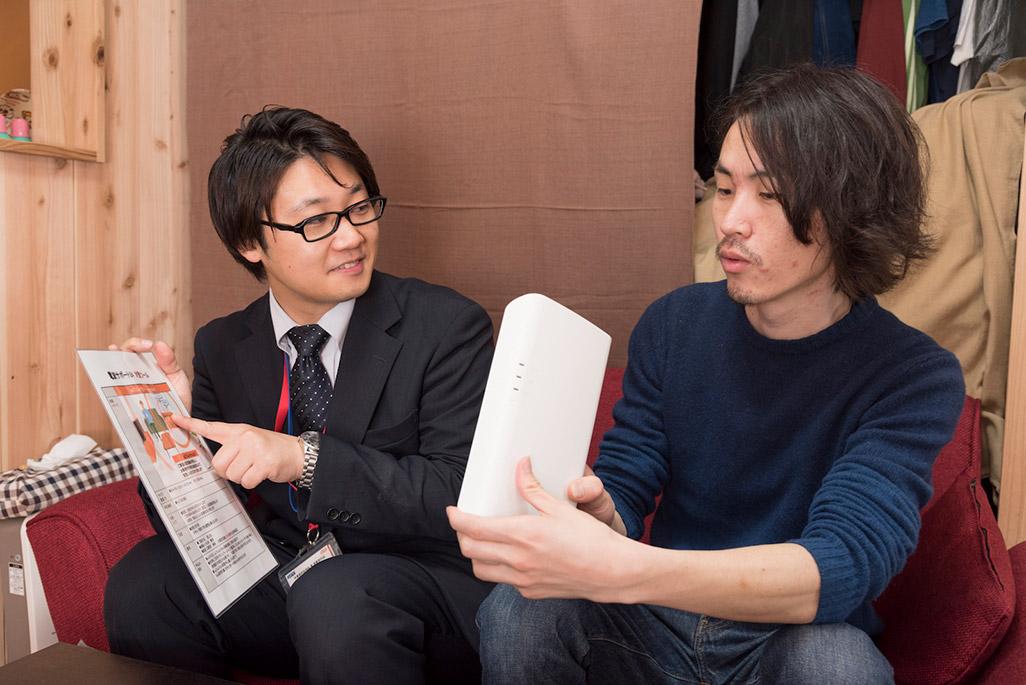 サービスの特徴を説明する須郷さんとauフェムトセルを眺めるライター