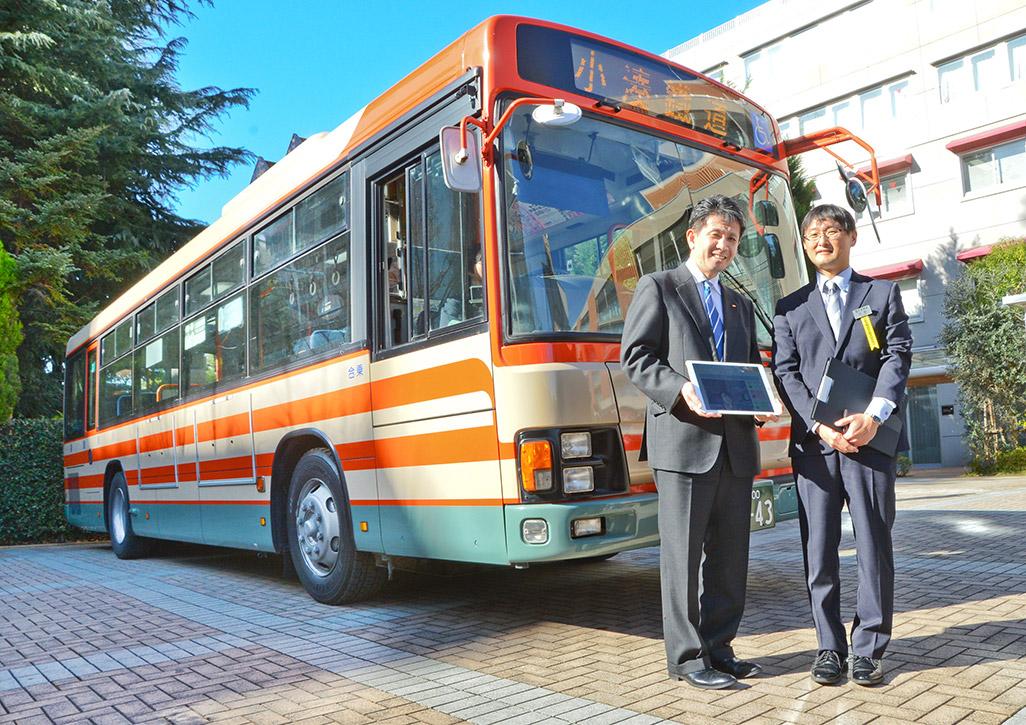 「小湊バス」の前で微笑む小湊鉄道 バス事業部の小杉直次長とKDDI株式会社 ビジネスIoT推進本部の原田圭悟