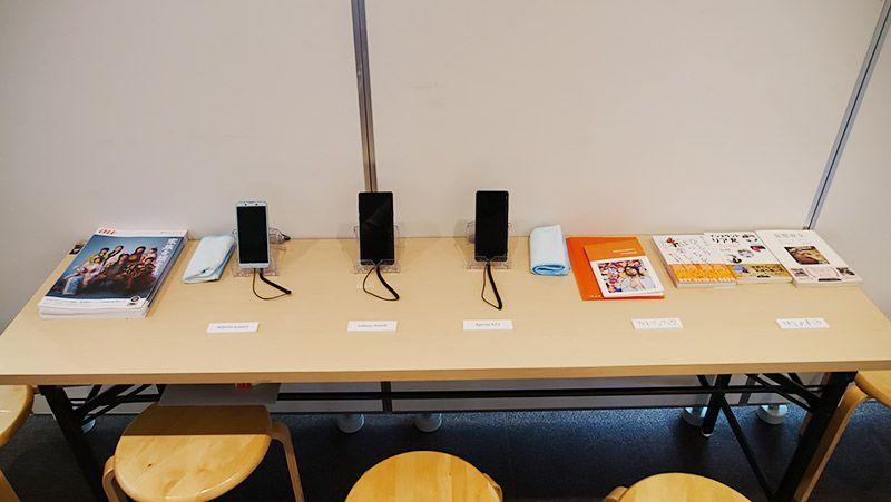 写真展にて展示されたスマートフォン、フォトブック、書籍など