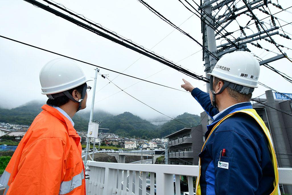 光ケーブルを電柱づたいのルートに切り替えることを検討する作業着姿の2人の男性