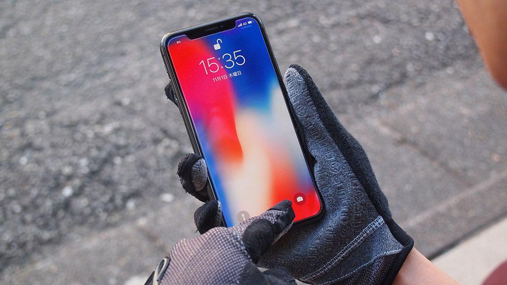 手袋をはめたまま、iPhone Xのロックを解除する男性