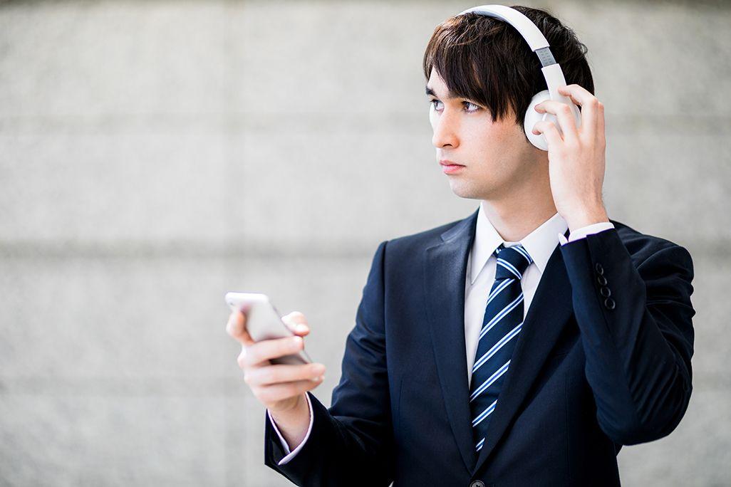 街中でノイズキャンセリングヘッドホンを着用した男性