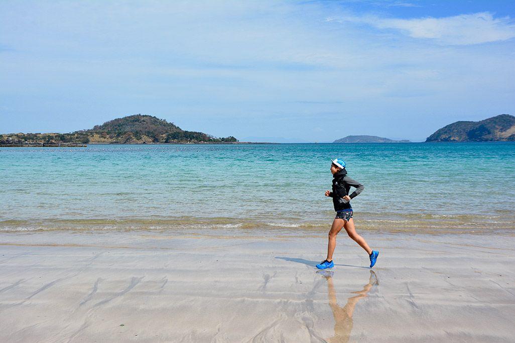 小値賀島の柿の浜海水浴場を走る浦谷美帆さん