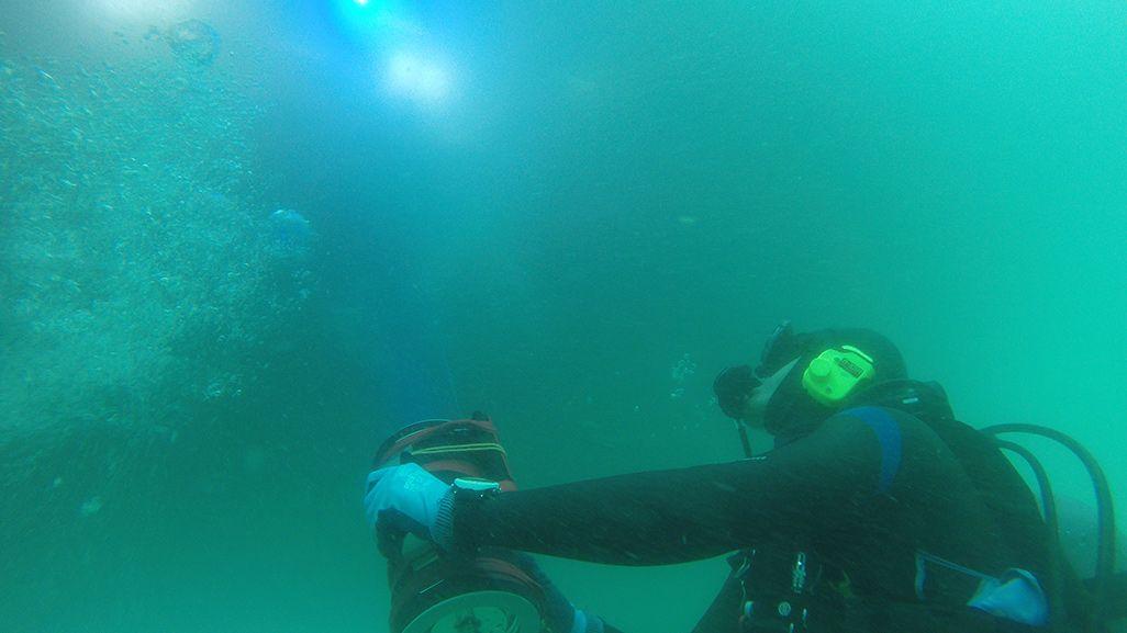 陸側の装置の光を水中で受けるダイバー
