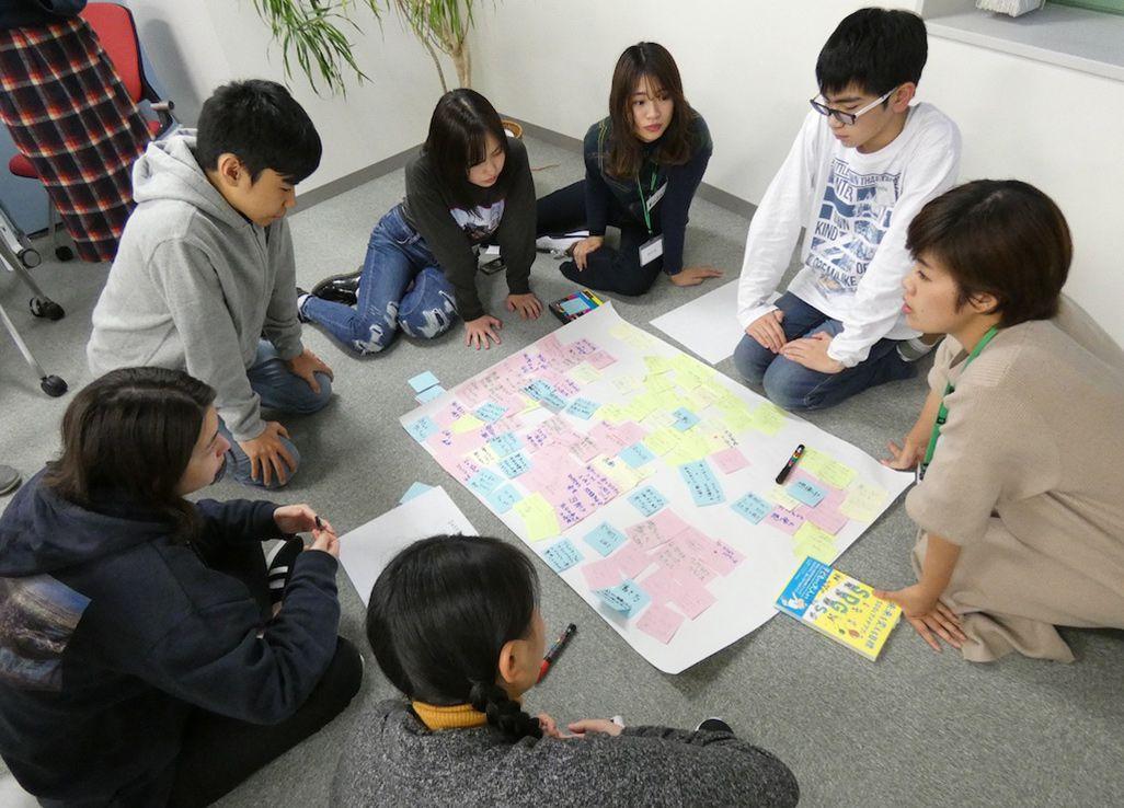 映像制作ワークショップでメモをもとに議論する参加者