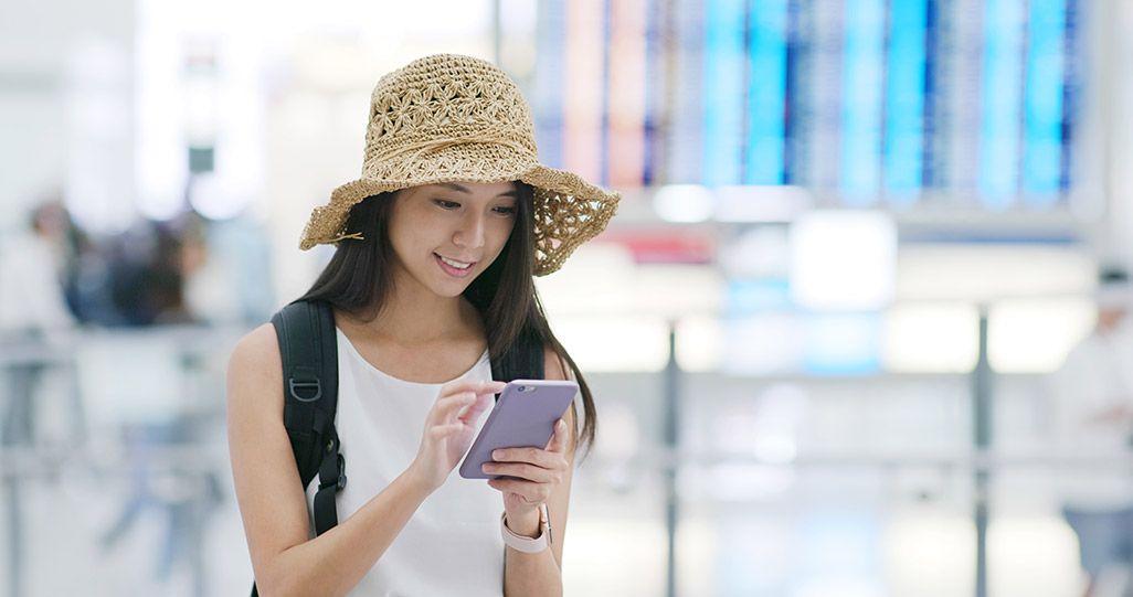 空港でスマートフォンを利用する女性
