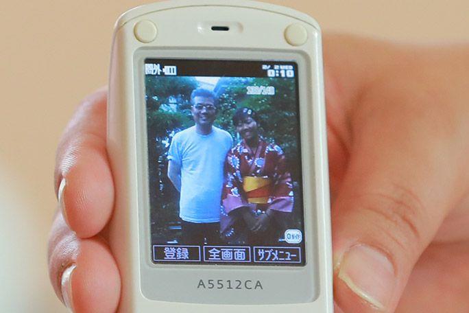 「おもいでケータイ再起動」で復活したケータイのディスプレイに映し出された父と娘