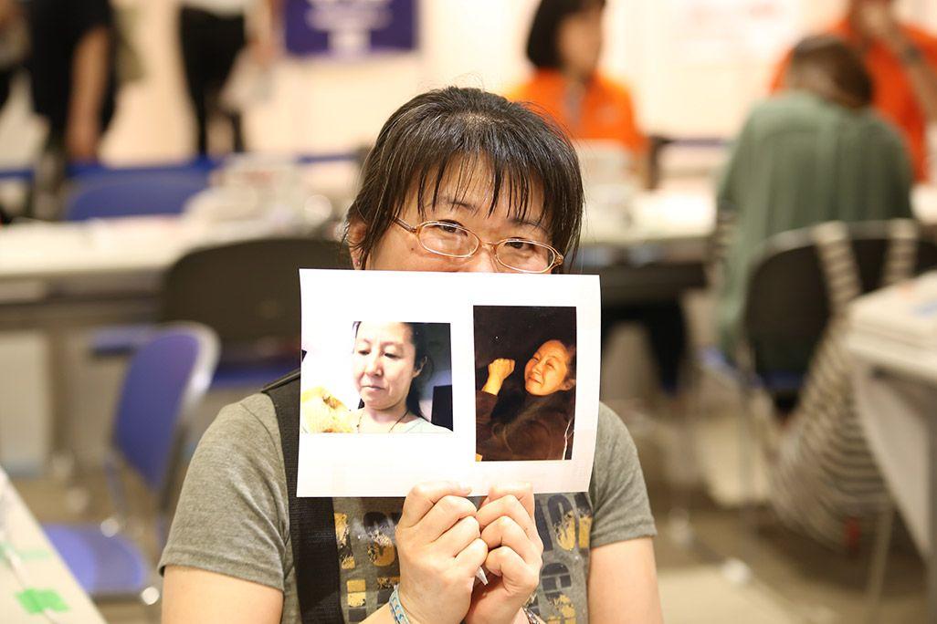 「おもいでケータイ再起動」で復活したガラケーからの写真を手に微笑む女性