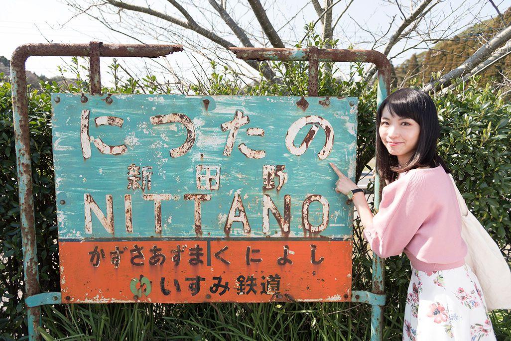 いすみ鉄道「新田野駅」の駅名標を指さす乗り鉄アイドルの伊藤桃