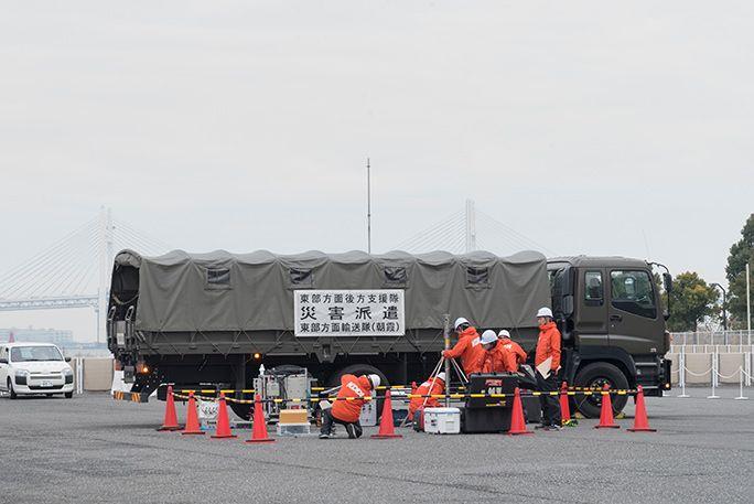 KDDIの災害対策公開訓練にて、自衛隊と連携して可搬型基地局を運んで設営する
