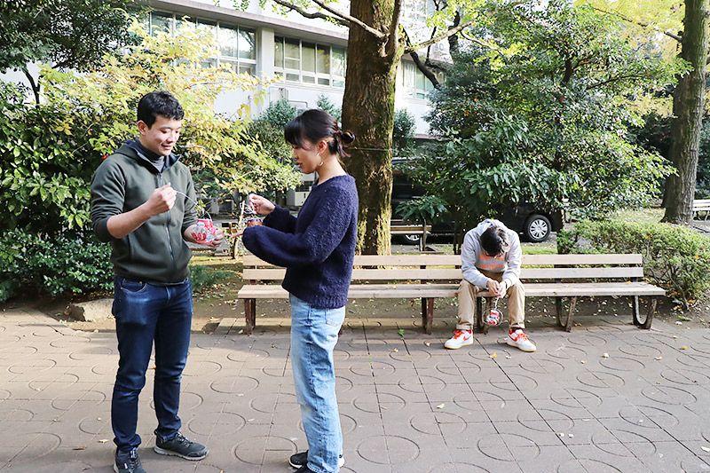 空き缶風車を見せ合う大学生2名と、疲れて再びベンチに座る地主