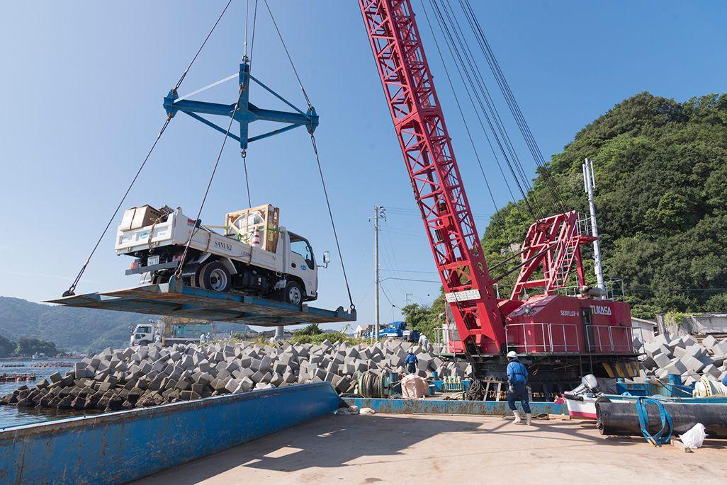 パラボラなど資材を積んだトラックに島に下ろす