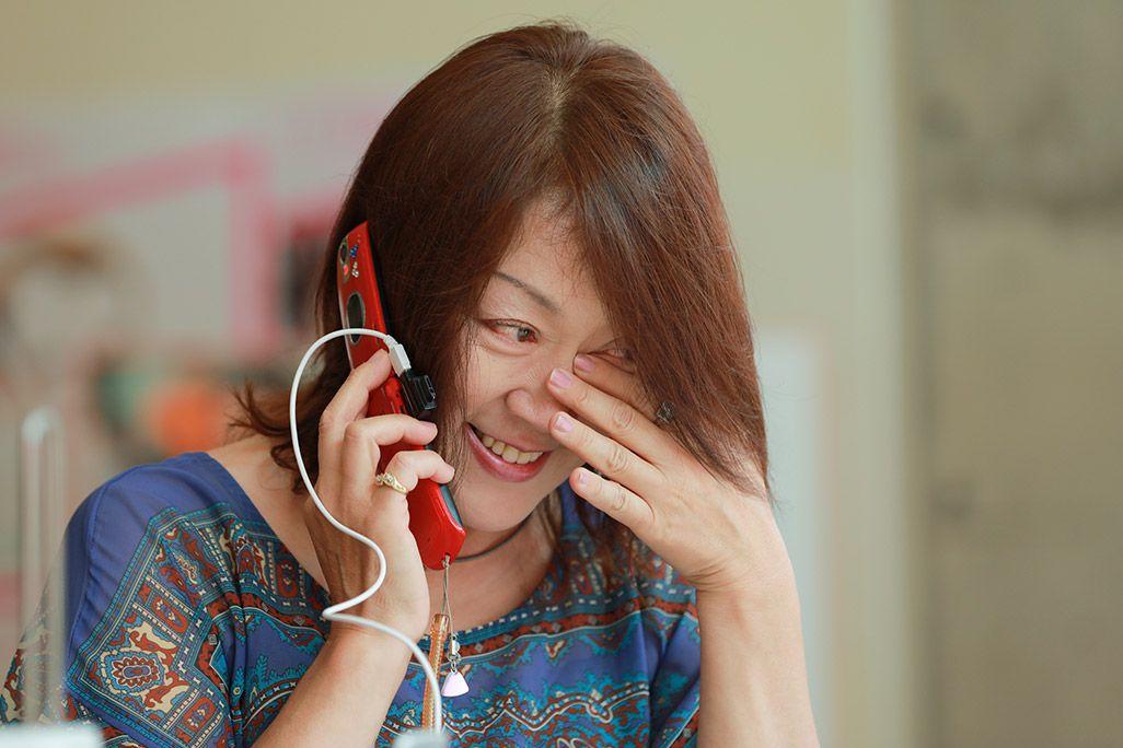 「おもいでケータイ再起動」で再起動したケータイに涙が止まらない女性