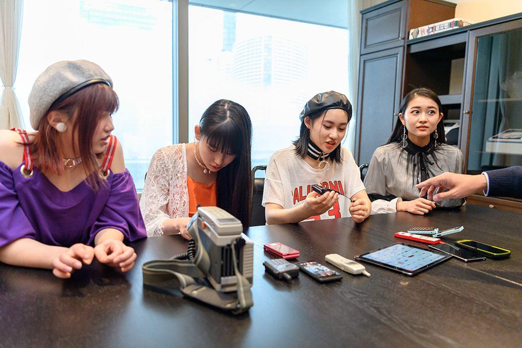 古い携帯電話の説明を受けるアンジュルムの和田彩花、佐々木莉佳子、笠原桃奈、竹内朱莉