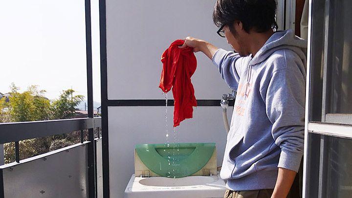 洗濯機からびちょびちょのTシャツを取り出すライターの地主