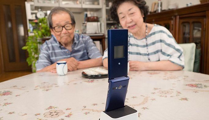 充電ホルダにのった、高齢者向けのケータイ「かんたんケータイ KYF38」で通話する夫婦