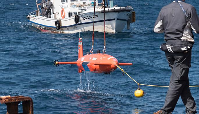 「Round2実海域競技」への進出を果たした「記念盾」を手に決意を新たにするKDDI総合研究所の西谷明彦と小島淳一