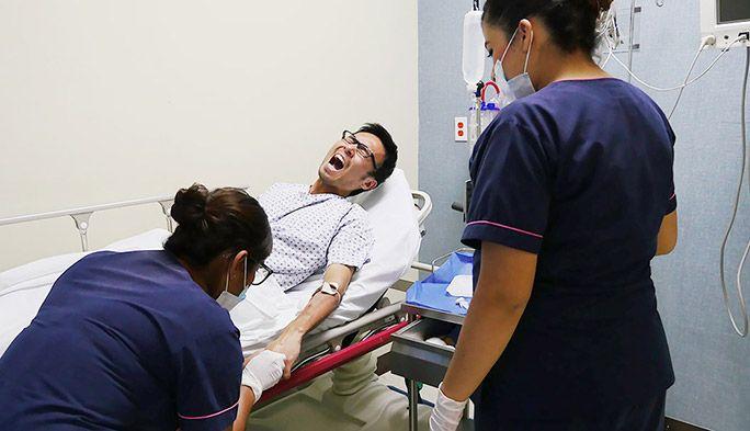病院のベッドで治療を受けるライターの地主恵亮